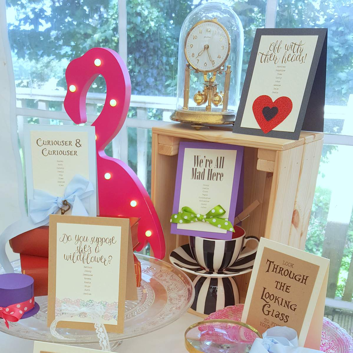 a display of printed cards and props that make a table plan for an alice in wonderland inspired wedding