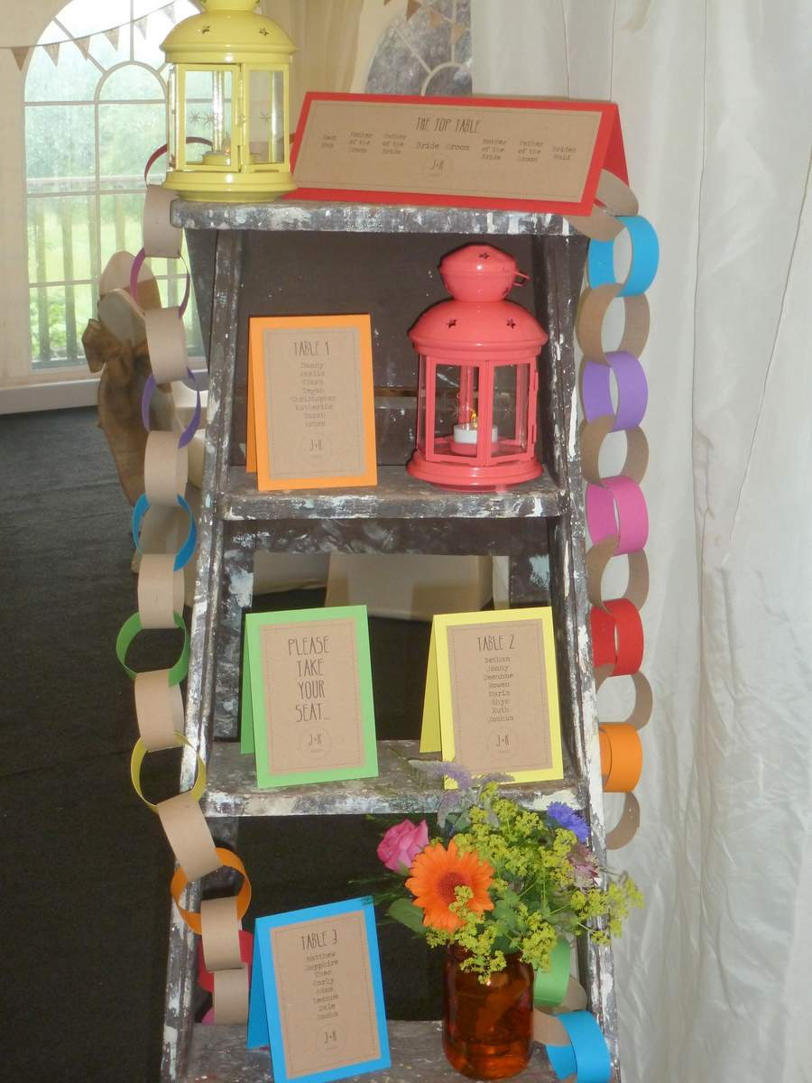 Brown kraft cards with colourful backings, printed with names and placed on a vintage step ladder to create a wedding table plan