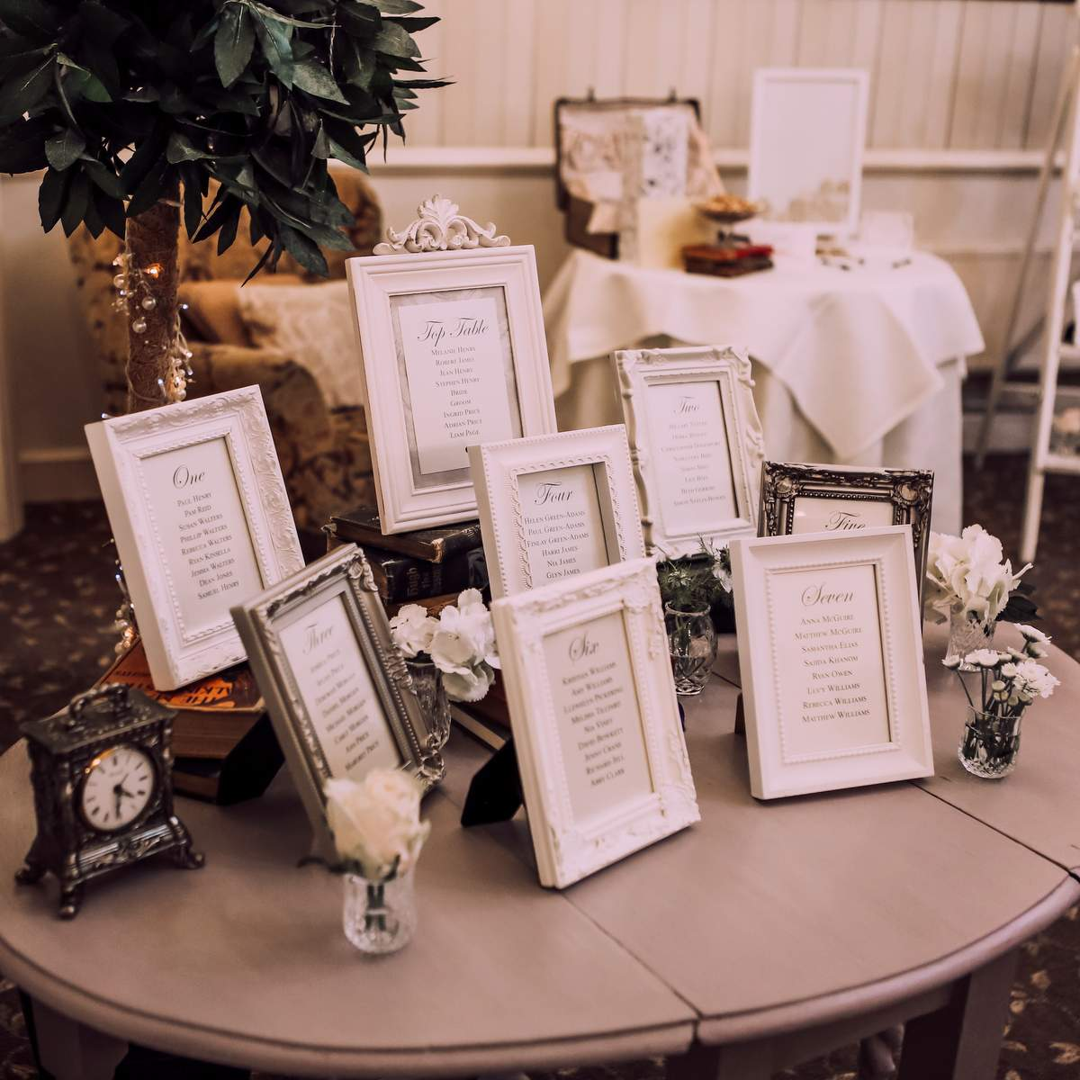 a display of vintage style white photo frames making up a wedding seating plan