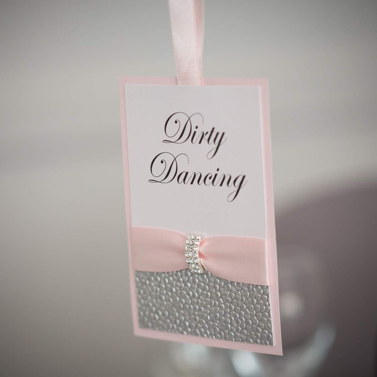 Bespoke wedding table name in silver and pink, hanging from a tall wedding table centre