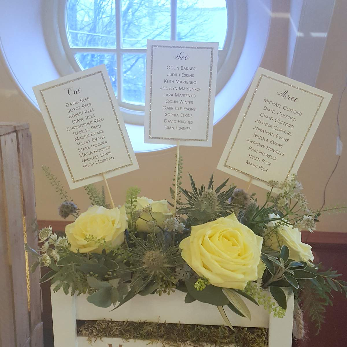 Wedding table plan cards, mounted on stick and sticking out of a rustic crate full of fresh flowers