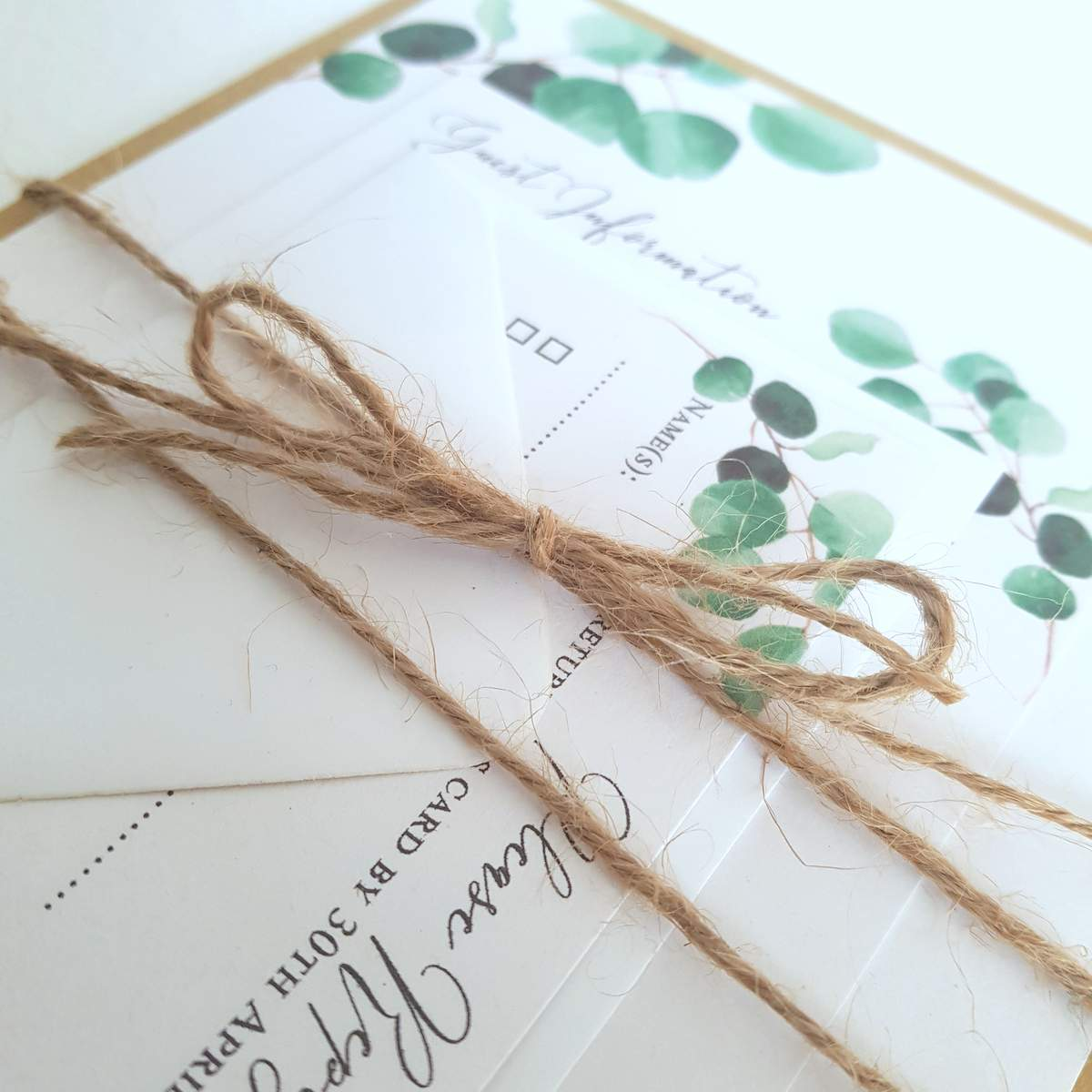A modern wedding invitation suite. White card printed with a graphic eucalyptus leaf print, all the cards are tied together with juste twine
