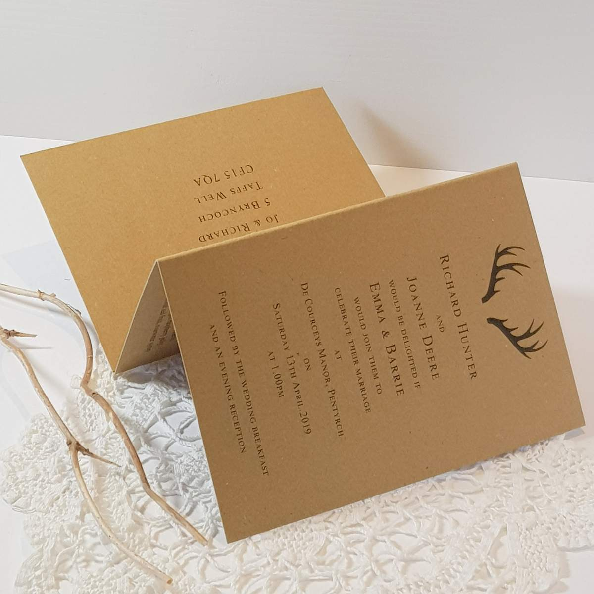 A concertina style wedding invitation made from recycled brown kraft card, featuring a printed stag antler design