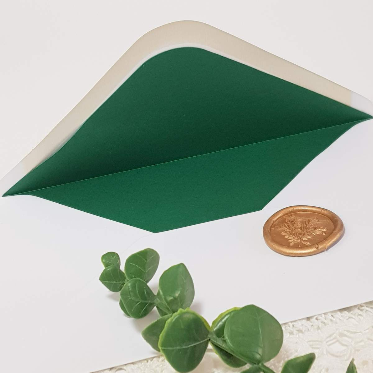 wedding invitation envelope with a dark green coloured liner and a gold wax seal